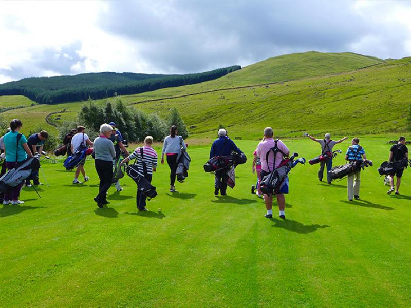Group of golfers walking across the course
